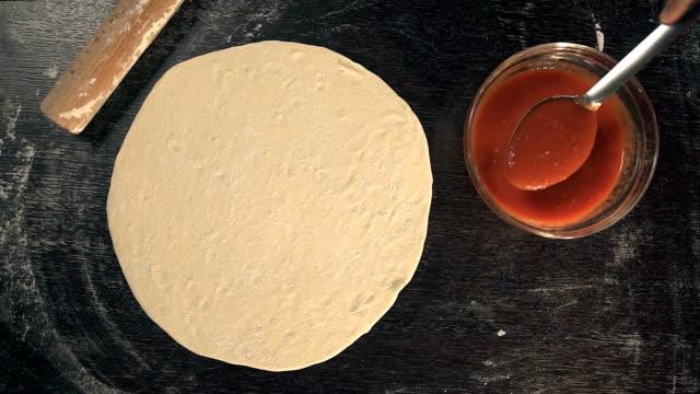Chef spreading tomato sauce. Making Pizza video