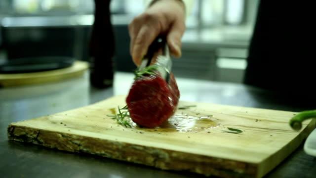 Chef sprinkles spice steak video