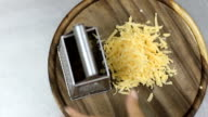 chef take off grating yellow cheese with metal grater from table video