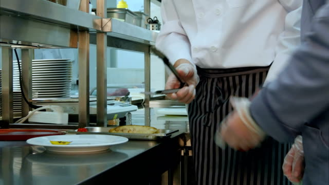 Chef teaching cook trainee how to serve the cooked dish properly video