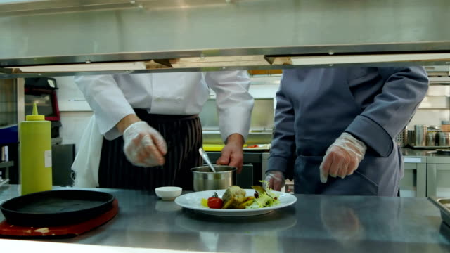 Chef teaching young trainee how to serve the sauce video