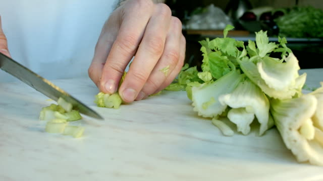 Chefs hands cutting a fresh green celery leaf. video