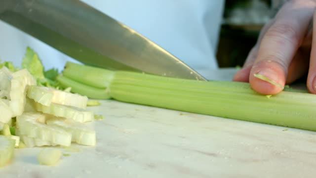 Chefs hands cutting a fresh green celery leaf. video