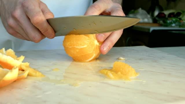 Chefs hands cutting a fresh orange. video