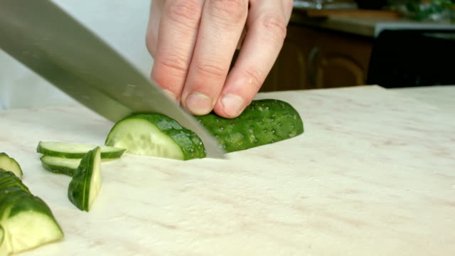 Chefs hands cutting a green fresh cucumber. video