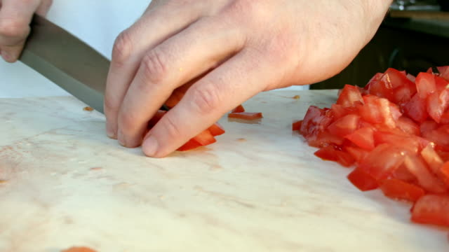 Chefs hands cutting a red fresh tomato. video
