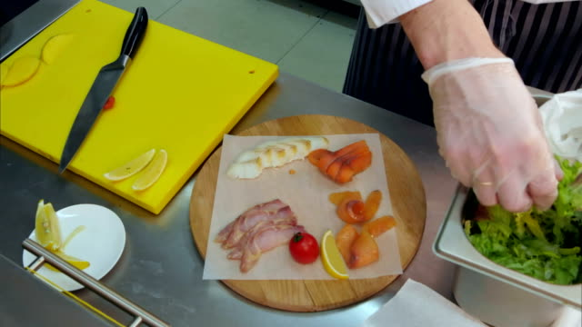 Chef's hands in gloves putting salad on a wooden platter with different meat video