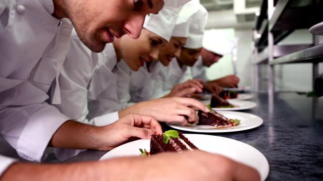Chefs standing in a row garnishing dessert plates video