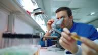 Chemist using microscope in chemistry laboratory. Scientist looking microscope video