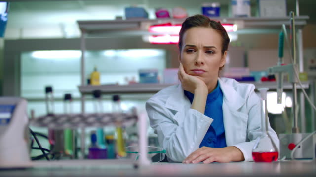 Chemist woman thinking in chemical lab. Female chemist in chemistry lab video