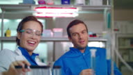 Chemistry scientist have fun at work. Chemical researchers smilling in lab video