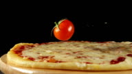Cherry tomatoes fall on a pizza on a black background video