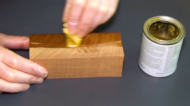 Cherry wood. The bar of solid wood is covered with stain. The girl covers a bar of rare wood with lacquer. The joinery impregnates the wood with wax. Gray background video
