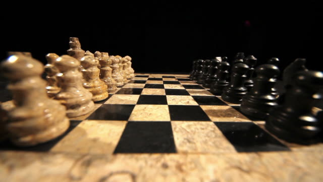 A chess board and its figures lined up for a new game start and a man making his first move with a black pawn video