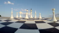 Chess board with figures and clouds concept, time lapse video