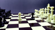 Chess board with pieces arranged at the beginning of a game , and unexpected opening with white and black pawns switching sides and  advancing towards the center of the board video