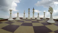 Chess pieces under cloudy sky, time lapse video