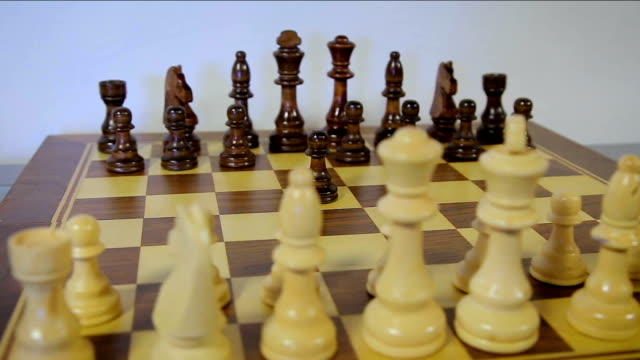 chessboard and chess pieces. Tracking shot, Circular camera flight. closeup wooden chess board business concept, handmade chess. opening move with a black pawn video