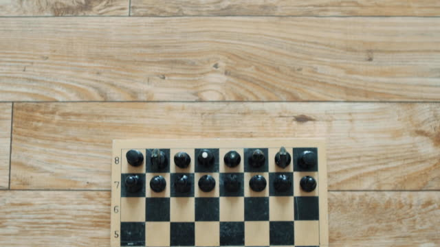 Chessboard and its figures lined up to start the game, view from above and move from top to bottom, High Angle chess board video