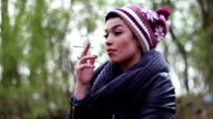 A chic adolescent girl with a funny cap enjoying smoking a cigarette video