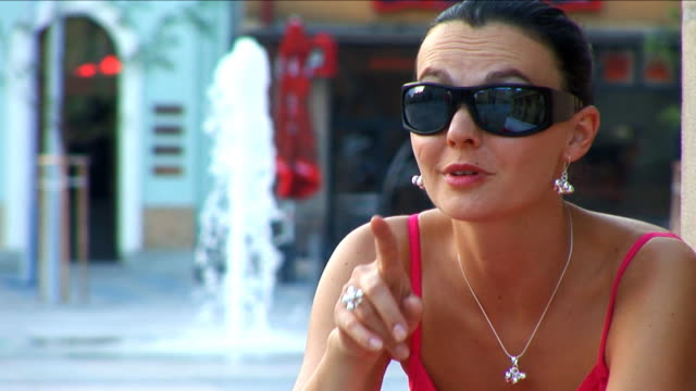 Chic designer girl sitting in the town square video
