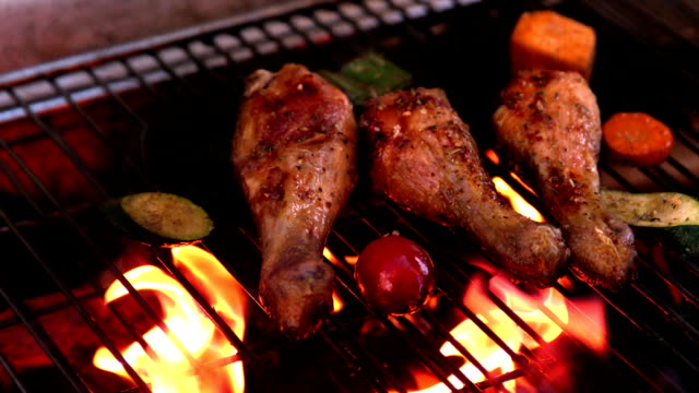 Chicken drumsticks being cooked on flaming barbecue video