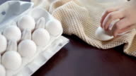 Chicken eggs in carton on kitchen table. Hand takes out eggs from carton video