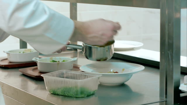 Chief adding sauce and herbs to prepared dishes video