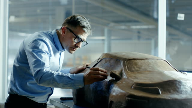 Chief Automotive Designer with Rake Sculpts Futuristic  Car Model from Plasticine Clay. He Works in a Special Studio Located In a Large Car Factory. video