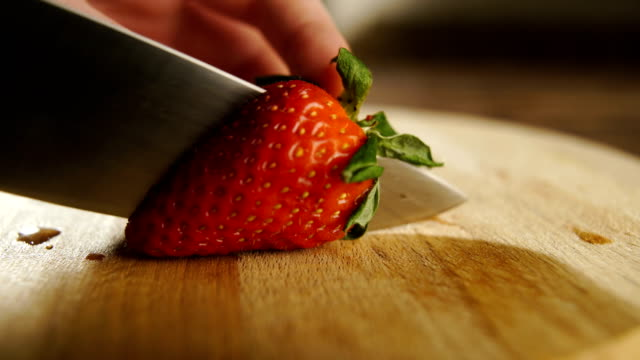 Chief cuts strawberry on professional kitchen video