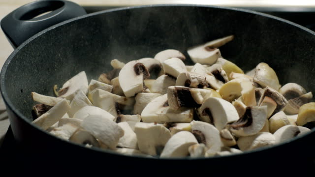 Chief drops button mushrooms to the pan with oil and onion. Slow motion video