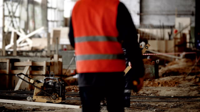 Chief engineer at an industrial facility. The man communicates with the foreman and compares with the project plan video