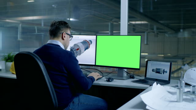 Chief Male Engineer Designs 3D Turbine/ Engine For a Big Industrial Company, His Second Display Shows Mock-up Green Screen Computer. Out of the Office Window Big Factory is Seen. video