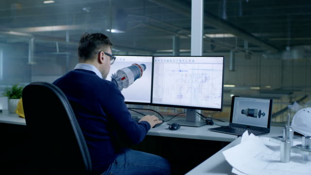 Chief Male Engineer Designs on 3D Model of a Turbine or Engine Part. Second Screen Shows Technical Blueprints. Out of the Office Window Big Factory is Seen. video