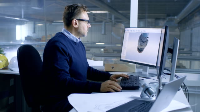 Chief Male Engineer Working on Big Technical Project Creating 3D Turbine/ Engine Model on His Personal Computer. He Uses Cad Software.Out of the Office Window Big Factory is Seen. video
