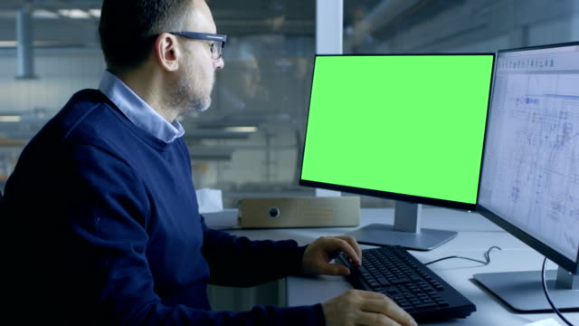 Chief Male Engineer Working on Technical Project on His Person Computer. Second Display Shows Mock-up Green Screen. Out of the Office Window Big Factory is Seen. video