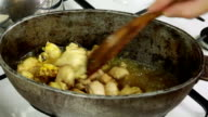 Chief mixing meat with spice in simmering oil video
