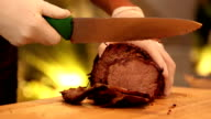 Chief slicing roasted piece of meat. video