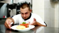 chief-cooker evaluates finished dish, professional kitchen restaurant chef dressed in uniform working, He is looking for food before serving customers video