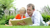 Child and father watching album/book in the garden video
