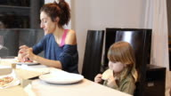 child and mother eating pizza at home video