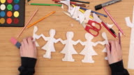 Child cutting chain fairy figures out of paper video