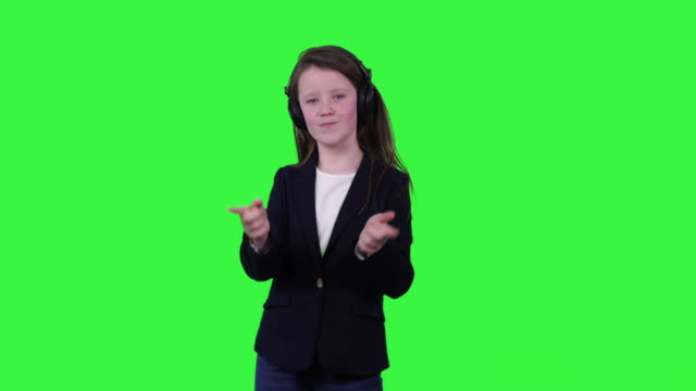 Child dancing with earphones on chromakey video