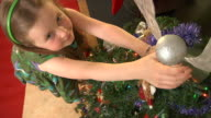 Child decorating Christmas tree video