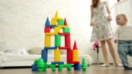 Child destroys house of colored blocks. Concept. video
