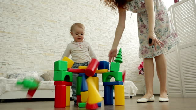 Child destroys house of colored blocks. video