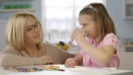 Child Doing Homework at Home. Mother Brings a Glass of Wather video