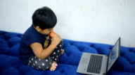 Child drink brain look laptop for entertainment. video
