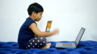 Child eat look laptop for entertainment. video