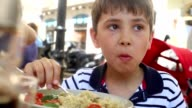 Child eating healthy quinoa meal. Young 8 year old boy eating healthy meal outdoors video